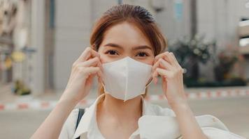 Exitosa empresaria asiática joven en ropa de oficina de moda usa mascarilla médica sonriendo y mirando a la cámara mientras está feliz de pie sola al aire libre en la ciudad moderna urbana. concepto de negocio en movimiento. foto