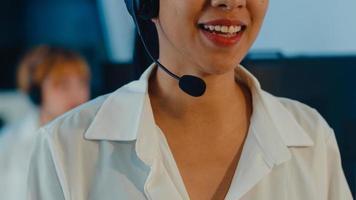 Primer plano de un joven equipo de centro de llamadas de Asia o un ejecutivo de servicio de atención al cliente que utiliza auriculares de computadora y micrófono, soporte técnico de trabajo en la oficina nocturna. concepto de trabajo de telemarketing o ventas. foto