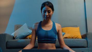 Jovencita asiática en ejercicios de ropa deportiva haciendo ejercicio y usando la computadora portátil para ver un video tutorial de yoga en la noche en casa. entrenamiento a distancia con entrenador personal, distancia social, concepto de educación en línea. foto
