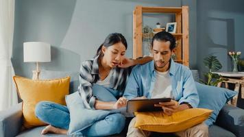 Feliz pareja joven y atractiva asiática, hombre y mujer, sentarse en el sofá, usar la tableta, comprar muebles en línea, decorar el hogar en la sala de estar de la nueva casa. joven casado mudanza concepto online comprador de casa. foto