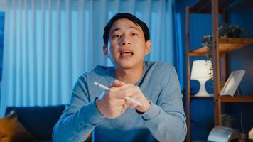 Asia empresario mirando el enfoque de la cámara en línea videollamada reunión asignación trabajo con colega en tableta en sala de estar en casa horas extras por la noche, trabajo desde casa concepto de pandemia de coronavirus. foto