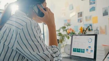 Joven mujer de negocios de Asia llame al teléfono móvil con colegas en la empresa sobre el plan de mercado de gráfico de gráfico de finanzas de trabajo en computadora portátil y tableta en casa. chica estudiante aprende en línea, trabaja desde el concepto de hogar. foto