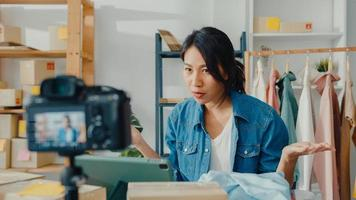 joven diseñadora de moda asiática que usa un teléfono móvil y recibe una orden de compra y muestra la ropa, grabando video en vivo en línea con la cámara. propietario de una pequeña empresa, concepto de entrega de mercado en línea. foto