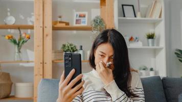 mujer asiática joven enferma mantenga medicina sentarse en el sofá videollamada con teléfono consulte con el médico en casa. chica toma medicamentos después de la orden del médico, cuarentena en casa, concepto de coronavirus de distanciamiento social. foto