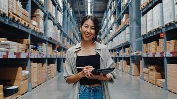 Retrato de joven y atractiva mujer de negocios de asia sonriendo encantadoramente mirando a la cámara sostenga el soporte de la tableta digital en el centro comercial minorista. distribución, logística, paquetes listos para embarque. foto