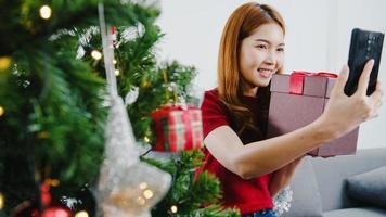 Joven mujer asiática con videollamada de teléfono inteligente hablando con pareja con caja de regalo de Navidad, árbol de Navidad decorado con adornos en la sala de estar en casa. festival de navidad y año nuevo. foto