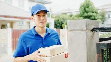 joven mensajero de entrega postal de asia con camisa azul que maneja cajas de paquetes para enviar al cliente en la casa y una mujer asiática recibe el paquete entregado al aire libre. concepto de entrega de alimentos de compras de paquete. foto