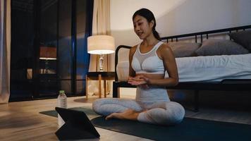 joven asiática en ejercicios de ropa deportiva haciendo ejercicio y usando la tableta para ver el video tutorial de yoga en la noche en casa. entrenamiento a distancia con entrenador personal, distancia social, concepto de educación en línea. foto