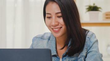 Retrato de ropa casual de mujeres de negocios inteligentes independientes usando laptop trabajando en el lugar de trabajo en la sala de estar en casa. feliz joven asiática relajarse sentado en la búsqueda de escritorio y hacer trabajo en internet. foto