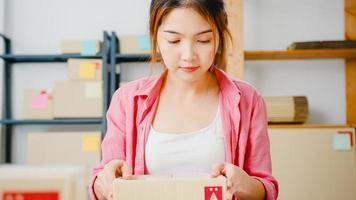 Producto de embalaje de empresaria joven empresaria de asia en caja de cartón entregar al cliente, trabajando en la oficina en casa. propietario de una pequeña empresa, puesta en marcha de la entrega del mercado en línea, concepto independiente de estilo de vida. foto