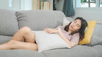 mujer asiática durmiendo en el sofá en la sala de estar, hermosa mujer japonesa usando tiempo de relajación acostado en el sofá en casa. estilo de vida de las mujeres de etnia latina e hispana en el concepto de casa. foto