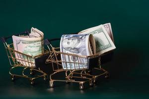 dólares en un carro sobre un fondo verde oscuro. finanzas y bancos. compras, descuentos, rebajas. foto