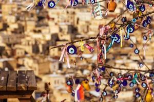 Blue evil eye, nazar boncugu, Turkish symbols hanging on a tree, Cappadocia photo