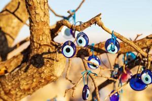 Blue evil eye, nazar boncugu, Turkish symbols hanging on a tree. Cappadocia photo