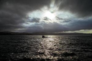 Pescador barcos de pesca en el Bósforo de Estambul en un amanecer brumoso. nubes lluviosas y clima oscuro foto