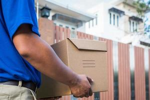 Repartidor azul con caja de cartón de paquete. foto