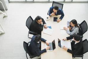 Vista superior del equipo de gente de negocios asiática analizando estadísticas financieras. Vista de ángulo alto de un equipo de empresarios reunión concepto corporativo de discusión de conferencia en la oficina. foto