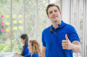 Customer support operator at work. Team Business and Delivery call center in office. Working with a headset in blue uniform while showing thumbs up. photo
