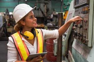 Trabajadora industrial trabajando y comprobando la máquina en una gran fábrica industrial con muchos equipos. foto