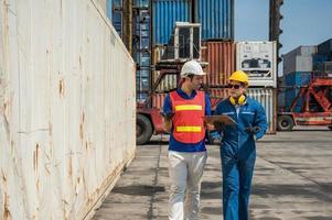 capataz y personal de los trabajadores portuarios que trabajan comprobando en el puerto de carga de contenedores con el portapapeles. concepto de envío de exportación de importación de logística empresarial. foto