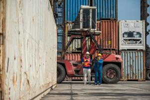 Foreman and dock worker staff working checking at Container cargo harbor holding clipboard. Business Logistics import export shipping concept. photo