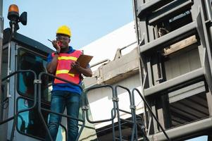 Black foreman worker working control the crane and forklift at Container cargo photo