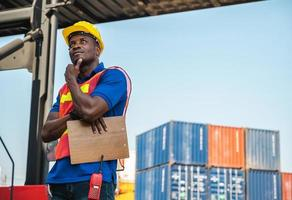 Black foreman worker working control the crane and forklift at Container cargo harbor to loading containers. African dock male staff for Logistics import export shipping concept. photo
