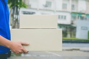 Cerrar repartidor en uniformes azules con caja de cartón de paquete. foto