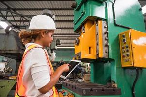 Female industrial worker working and checking machine in a large industrial factory with many equipment. photo