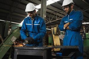 Trabajador industrial cortando metal y acero con muchas chispas foto