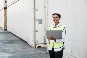 Black foreman woman worker working checking at Container cargo harbor holding laptop computer to loading containers. African dock female staff business Logistics import export shipping concept. photo