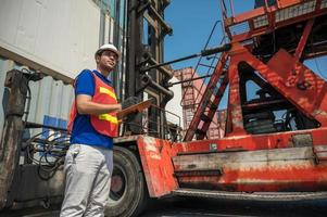 Foreman holding clipboard working at Container cargo harbor. Business Logistics import export shipping concept. photo