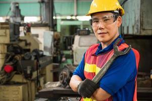 Los trabajadores industriales asiáticos están trabajando en proyectos en grandes plantas industriales con muchos dispositivos. foto