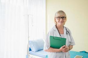 Senior woman doctor with clipboard standing near patient bed. Medical healthcare and doctor service in hospital. photo