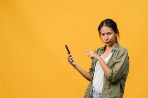 Pensando soñando a una joven asiática que usa el teléfono con expresión positiva, vestida con un paño casual sintiendo felicidad y de pie aislado sobre fondo amarillo. feliz adorable mujer alegre se regocija con el éxito. foto