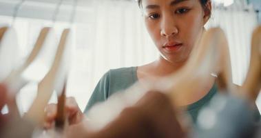 Bella y atractiva joven asiática eligiendo su ropa de moda en el armario de la sala de estar en casa o tienda. chica piensa qué ponerse camisa casual. Vestuario de casa o tienda de ropa, vestuario. foto