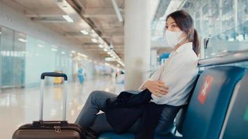Chica de negocios asiática caminar con equipaje sentada en un banco, esperar y buscar pareja para el vuelo en el aeropuerto. pandemia de covid de viajeros de negocios, distanciamiento social de viajes de negocios, concepto de viajes de negocios. foto