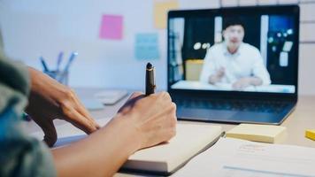 Asia empresaria usando laptop hablar con colegas sobre el plan en la reunión de videollamada en la sala de estar. trabajando desde casa por sobrecarga nocturna, trabajo a distancia, distanciamiento social, cuarentena por coronavirus. foto
