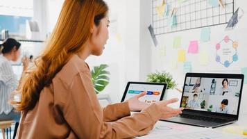 Los empresarios asiáticos que usan una computadora portátil hablan con sus colegas que discuten una lluvia de ideas de negocios sobre el plan en una reunión de videollamada en la nueva oficina normal. distanciamiento social de estilo de vida y trabajo después del virus corona. foto
