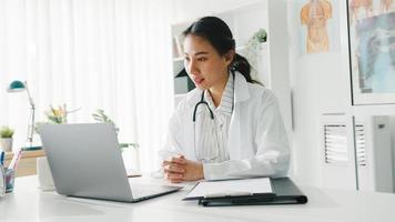 Joven doctora asiática en uniforme médico blanco con estetoscopio usando computadora portátil hablando por videoconferencia con el paciente en el escritorio en la clínica de salud u hospital. concepto de consulta y terapia. foto