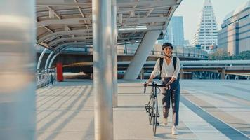Asian businesswoman go to work at office walk and smile wear backpack look around take bicycle on street around building on a city street. Bike commuting, Commute on bike, Business commuter concept. photo