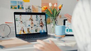 joven empleada de asia escucha al líder en la videollamada con diversos colegas multirraciales en línea con la computadora portátil en casa. la educación a distancia. alumna aprende en línea en casa, concepto de reunión en línea. foto