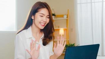 Mujer de negocios asiática joven que usa la videollamada del ordenador portátil que habla con la pareja mientras trabaja desde casa en la sala de estar. autoaislamiento, distanciamiento social, cuarentena por coronavirus en el próximo concepto normal. foto