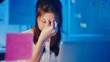 mujeres asiáticas independientes que usan una computadora portátil trabajan duro en la nueva oficina en casa normal. trabajando desde la sobrecarga de la casa por la noche, trabajo a distancia, autoaislamiento, distanciamiento social, cuarentena para la prevención del virus corona. foto