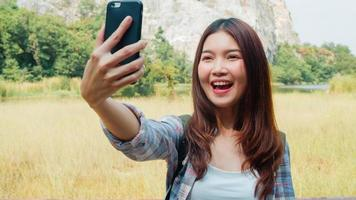 Cheerful young traveler Asian lady with backpack recording video vlog live streaming on phone upload in social media at mountain lake. Korean girl happy enjoy holiday trip. Lifestyle travel and relax. photo