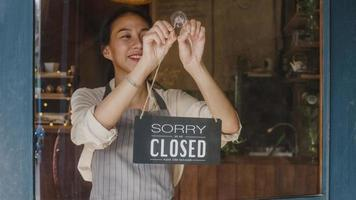 Young Asia manager girl changing a sign from closed to open sign on door cafe looking outside waiting for clients after lockdown. Owner small business, food and drink, business reopen again concept. photo