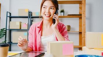 joven empresaria de asia mediante llamada de teléfono móvil que recibe la orden de compra y comprueba el producto en stock, trabaja en la oficina en casa. propietario de una pequeña empresa, entrega de mercado en línea, concepto independiente de estilo de vida. foto