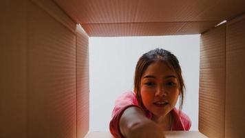 Emocionada joven asiática desempaqueta abriendo una enorme caja de cartón y mirando dentro de un nuevo regalo en casa. feliz clienta millennial satisfecha con la compra ordenada. entrega y concepto de compras en línea. foto