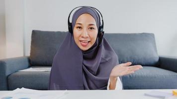 Asia dama musulmana usa audífonos usando una computadora portátil, hable con sus colegas sobre el plan en una reunión de videoconferencia mientras trabaja de forma remota desde su casa en la sala de estar. distanciamiento social, cuarentena por coronavirus. foto