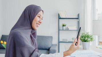 Young Asia muslim businesswoman using smart phone talk to friend by videochat brainstorm online meeting while remotely work from home at living room. Social distancing, quarantine for corona virus. photo